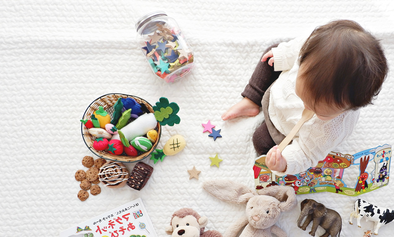 baby on blanket surrounded by toys